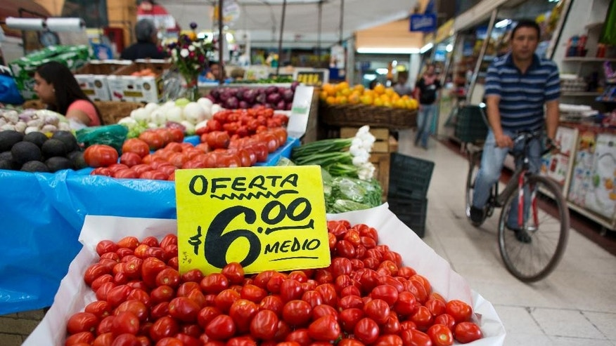 "A man bikes past vegetable stands inside Mercado Medellin in Mexico City, Friday, May 20, 2016. The tomatoes are marked down to the sale price of six pesos per half kilogram, or about .33 cents for one pound. Mexico is lowering its economic growth forecast for 2016, citing what it calls ""adverse"" international conditions including sluggish industrial production in the United States. (AP Photo/Rebecca Blackwell)"