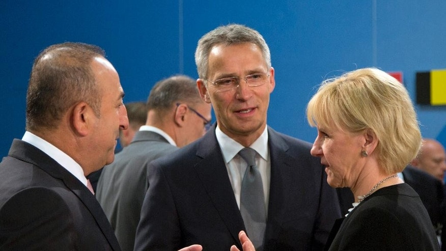 Swedish Foreign Minister Margot Wallstrom, right, speaks with Turkish Foreign Minister Mevlut Cavusoglu, left, and NATO Secretary General Jens Stoltenberg, center, during a meeting of the North Atlantic Council at NATO headquarters in Brussels on Friday, May 20, 2016. NATO's chief says the alliance has reached a broad agreement to seek another meeting with Russia before NATO heads of state and government meet in Warsaw this July. (AP Photo/Virginia Mayo)