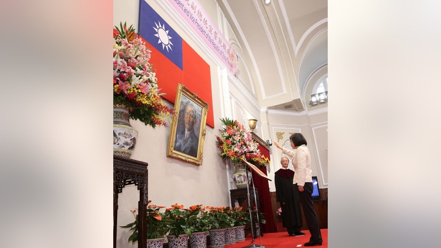 Standing in front of a portrait of the founding father of the Republic of China, R.O.C., Dr. Sun Yat-sen, Taiwan's President Tsai Ing-wen recites the oath of office during the swearing-in ceremony at the Presidential Office in Taipei, Taiwan May 20, 2016. Taiwan inaugurated Tsai Ing-wen as its first female president on Friday, returning the pro-independence Democratic Progressive Party to power amid new concerns over increasingly fractious relations with Beijing and a flagging economy. (Taipei Photojournalists Association/Pool Photo via AP)