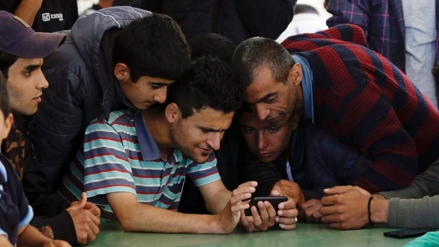 In this photo taken on Wednesday, April 27, 2016 Dishad Omer,  from Dohuk, Iraq, center, shows to other migrants and refugees the picture that he took with his cell phone when he was blocked by the Macedonian police along with other migrants at the border with Bulgaria, as he sits inside a building of a refugees and migrants center, in Petra village, northern Greece. Stranded refugees tell of being pushed back into Greece despite having made it further north through the Balkans when the borders were still open. (AP Photo/Gregorio Borgia)
