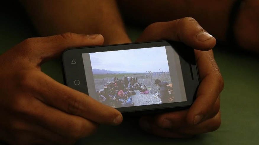 In this photo taken on Wednesday, April 27, 2016 Dishad Omer,  from Dohuk, Iraq, shows to journalists the picture that he took with his cell phone when he was blocked by the Macedonian police along with other migrants at the border with Bulgaria, as he sits inside a building of refugees and migrants center, in Petra village, northern Greece. Stranded refugees tell of being pushed back into Greece despite having made it further north through the Balkans when the borders were still open. (AP Photo/Gregorio Borgia)