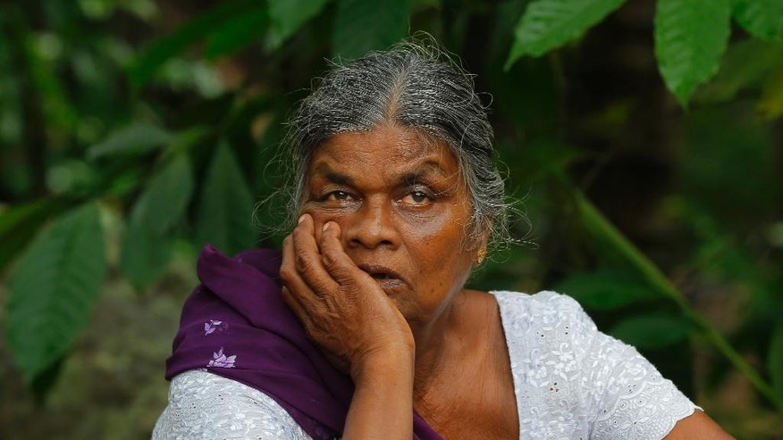 A relative of a missing Sri Lankan family watches as army soldiers search for victims under the debris of a house in Elangapitiya village in Aranayaka, some 72 kilometers (45 miles) north of Colombo, Sri Lanka, Thursday, May 19, 2016. Heavy rains Thursday continued to pound the central Sri Lankan region where at least three villages have already been swallowed by mountains of mud, forcing army soldiers and police to suspend rescue work. (AP Photo/Eranga Jayawardena)