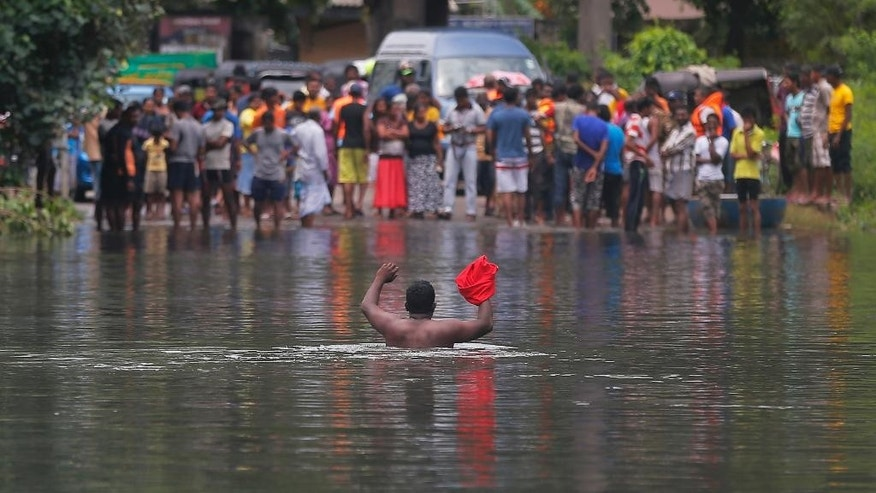 A Sri Lankan man crosses a submerged road in Wellampitiya, outskirts of Colombo, Sri Lanka, Friday, May 20, 2016. The weeklong rains have caused chaos across Sri Lanka, unleashing deadly landslides and driving tens of thousands from their homes. (AP Photo/Eranga Jayawardena)