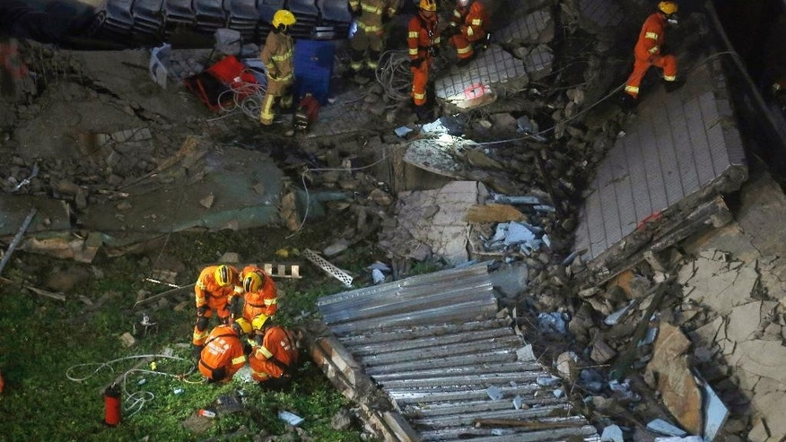Firefighters walk through the debris of the collapsed section of a building at the City University's campus in Hong Kong, Friday, May 20, 2016. The roof of an indoor hall at university's sports centre collapsed where three people were injured. (AP Photo/Kin Cheung)