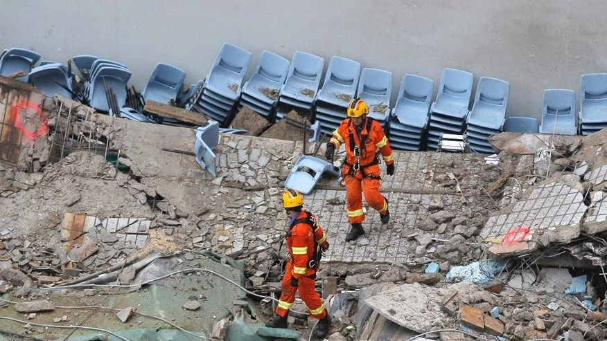Two firefighters walk through the debris of the collapsed section of a building at the City University's campus in Hong Kong, Friday, May 20, 2016. The roof of an indoor hall at university's sports centre collapsed where three people were injured. (AP Photo/Kin Cheung)