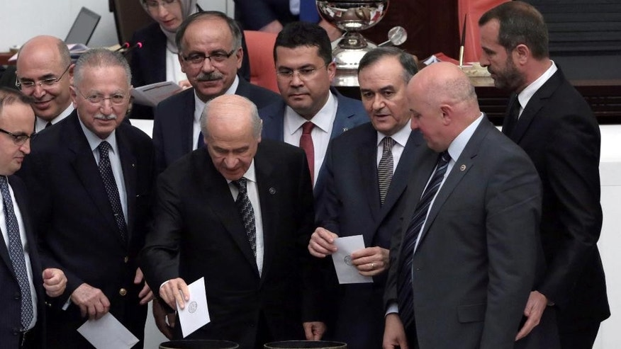 Opposition Nationalist Movement Party leader Devlet Bahceli, centre, votes at the parliament in Ankara, Turkey, Friday, May20, 2016. Turkey's parliament vote a government-backed constitutional amendment that would strip some legislators of immunity. It targets pro-Kurdish parliamentarians and could lead them to be tried on terror charges.(AP Photo/Burhan Ozbilici).