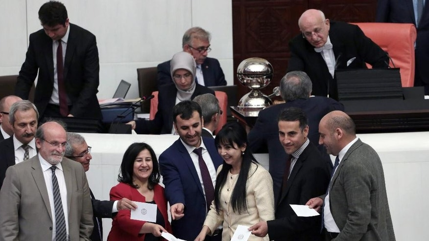 Pro-Kurdish Peoples' Democracy Party legislators vote at the parliament in Ankara, Turkey, Friday, May20, 2016. Turkey's parliament vote a government-backed constitutional amendment that would strip some legislators of immunity. It targets pro-Kurdish parliamentarians and could lead them to be tried on terror charges.(AP Photo/Burhan Ozbilici).