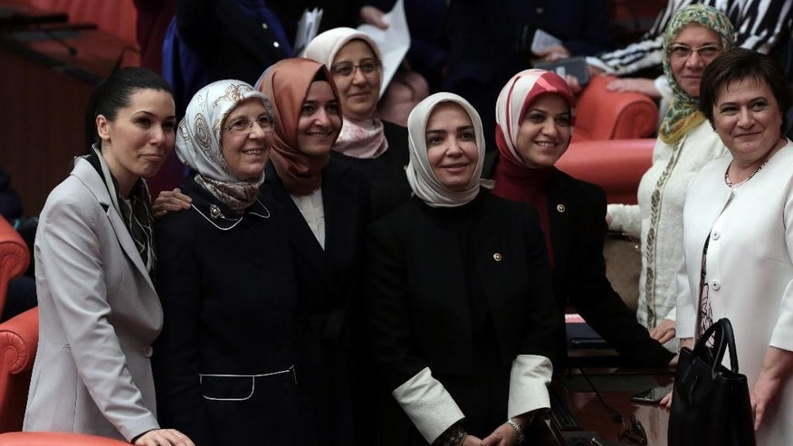 Ruling party legislators pose for a selfie photograph at the parliament in Ankara, Turkey, Friday, May 20, 2016. Turkey's parliament vote a government-backed constitutional amendment that would strip some legislators of immunity. It targets pro-Kurdish parliamentarians and could lead them to be tried on terror charges.(AP Photo/Burhan Ozbilici).