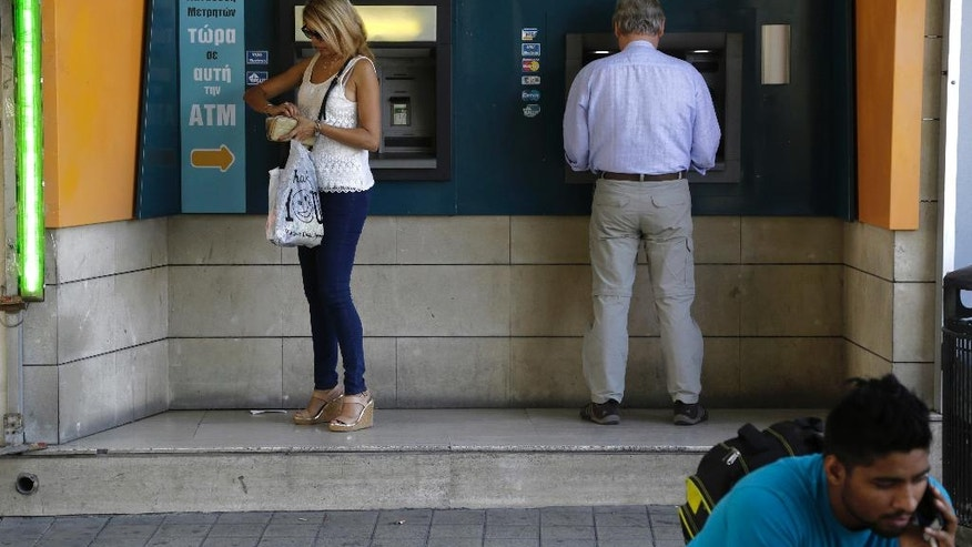 A man, right, speaks on his mobile phone as people use ATM machines outside a bank of Cyprus' branch in central capital Nicosia, eastern Mediterranean island of Cyprus, on Friday, May, 20, 2016. Knuckling down and doing away with wasteful spending while avoiding burdening working folks with more taxes helped Cyprus wrap up a three-year, multibillion euro rescue plan and emerge with solid growth and a dropping, but still high unemployment rate. (AP Photo/Petros Karadjias)