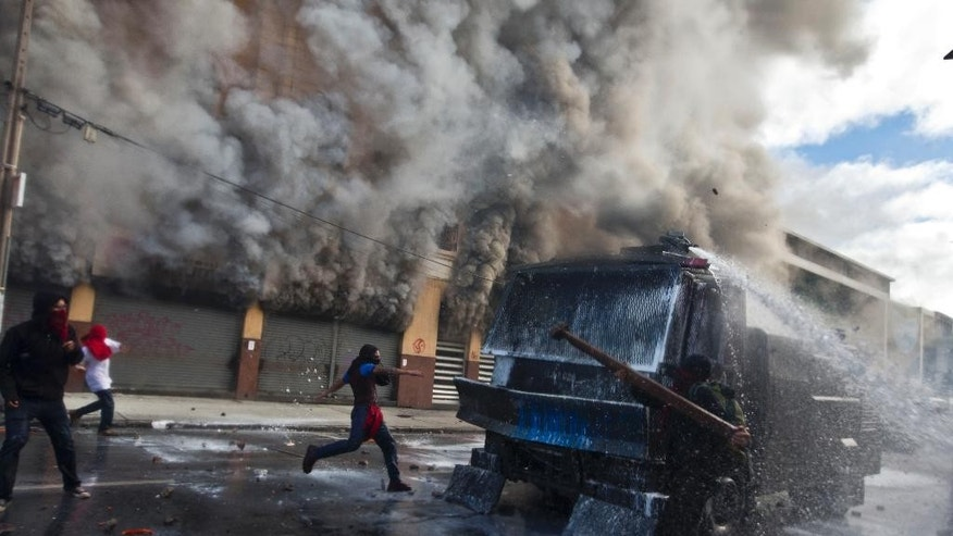 Masked protesters attack a police water canon in front of a burning pharmacy near Congress where President Michelle Bachelet was presenting the state-of-the-nation report, in Valparaiso, Chile, Saturday, May 21, 2016. The anti-government protest began as a peaceful march but turned rough as some demonstrators threw rocks at police and gasoline bombs at buildings, resulting in the death of one man who reportedly died of asphyxiation. (AP Photo/Esteban Felix)