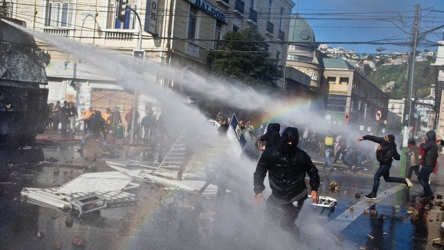 Masked protesters throw stones at a water cannon as police respond with high-pressure blasts of water, near Congress where President Michelle Bachelet was presenting the state-of-the-nation report, in Valparaiso, Chile, Saturday, May 21, 2016. The anti-government protest began as a peaceful march but turned rough as some demonstrators threw rocks at police and gasoline bombs at buildings, resulting in the death of one man who reportedly died of asphyxiation.(AP Photo/Esteban Felix)