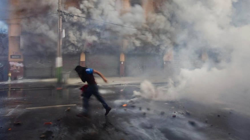 A masked protester runs from police responding with tear gas and high-pressure blasts of water, near Congress where President Michelle Bachelet was presenting the state-of-the-nation report, in Valparaiso, Chile, Saturday, May 21, 2016. The anti-government protest began as a peaceful march but turned rough as some demonstrators threw rocks at police and gasoline bombs at buildings, resulting in the death of one man who reportedly died of asphyxiation. (AP Photo/Esteban Felix)