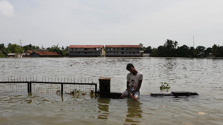 A Sri Lankan man sits on top of a partially submerged wall in Wellampitiya, outskirts of Colombo, Sri Lanka, Friday, May 20, 2016. Hundreds of boats plied deep floodwaters that have inundated thousands of homes in the Sri Lankan capital, delivering aid and rescuing the elderly and sick from rooftops as forecasters warned of more heavy rain. (AP Photo/Eranga Jayawardena)