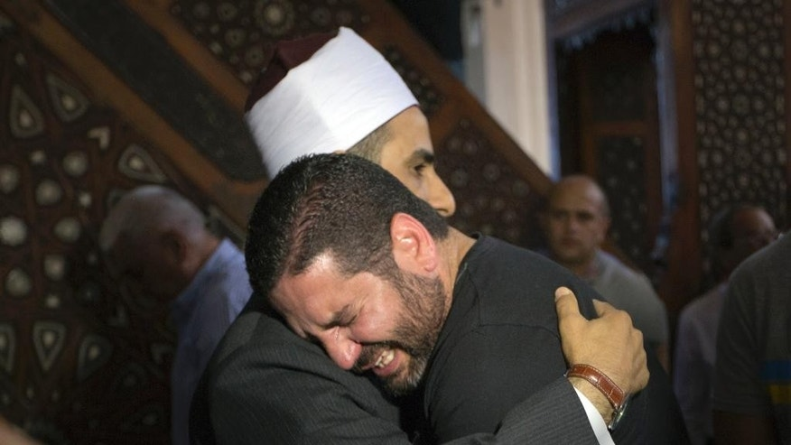 The Imam of al Thawrah Mosque, Samir Abdel Bary, gives condolences to Tarek Abu Laban, center, who lost four relatives, all victims of Thursday's EgyptAir plane crash, following prayers for the dead, at al Thawrah Mosque, in Cairo, Egypt, Friday, May 20, 2016. The Airbus A320 plane was flying from Paris to Cairo with 66 passengers and crew when it disappeared early Thursday over the Mediterranean Sea. (AP Photo/Amr Nabil)