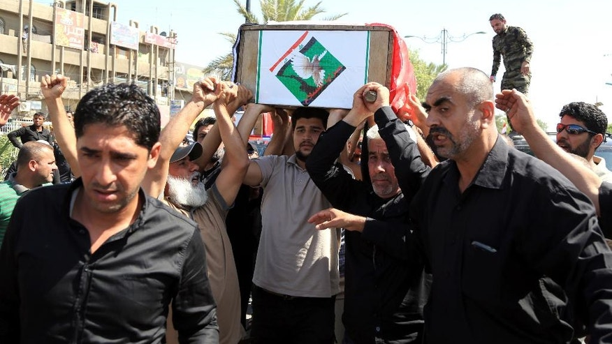 Mourners carry the Iraqi flag-draped coffin of a protester killed outside Baghdad's highly fortified Green Zone on Friday, during his funeral procession in Baghdad, Iraq, Saturday, May 21, 2016. On Friday Iraqi security forces have fired tear gas and gunshots in the air as thousands of Shiite protesters stormed Baghdad's heavily secured Green Zone, rushing toward the prime minister's office and parliament building. (AP Photo/Karim Kadim)