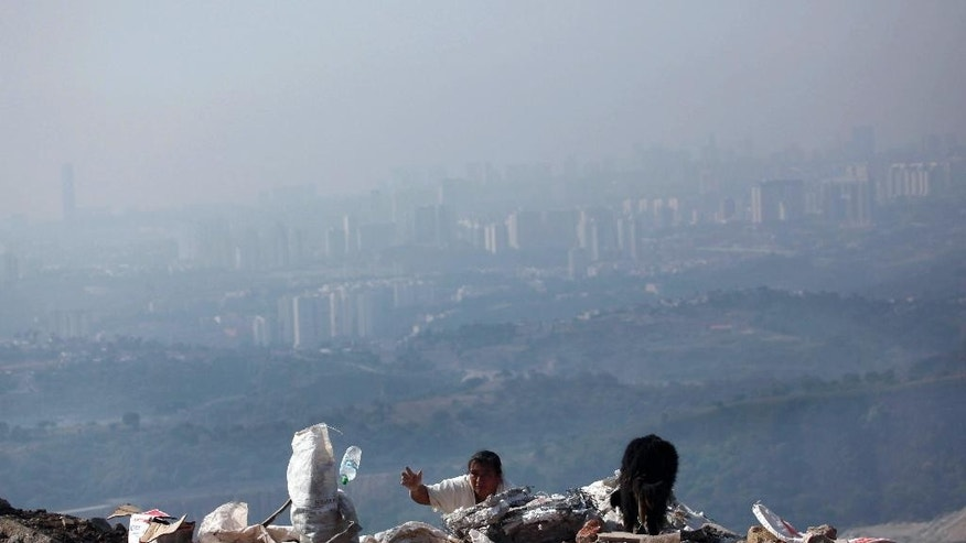 A woman combs though trash, looking for recyclable items, as a cloud of air pollution obscures the Mexico City skyline, Saturday, May 21, 2016. Mexican authorities have issued a new smog alert for the capital after ozone levels rose to almost twice acceptable limits. It's the fifth time this year that Mexico City has seen such an alert, which triggers additional restrictions on automobile usage. On Saturday 40 percent of vehicles have been barred from the streets of the capital and the surrounding suburbs. (AP Photo/Marco Ugarte)