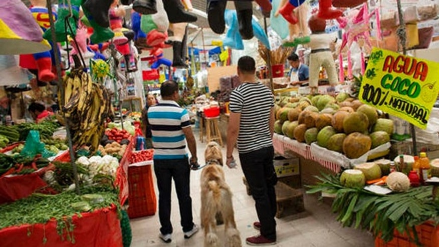 "Men shop along with their dog inside Mercado Medellin in Mexico City, Friday, May 20, 2016. Mexico is lowering its economic growth forecast for 2016, citing what it calls ""adverse"" international conditions including sluggish industrial production in the United States. (AP Photo/Rebecca Blackwell)"