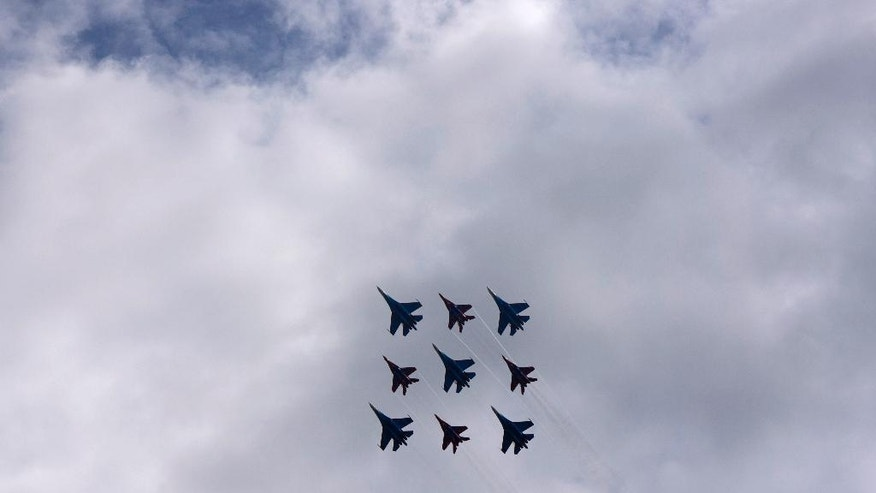 The Russian military's Strizhi, The Swifts, and Russkiye Vityazi, the Russian Knights, aerobatic teams perform during an air show at the Kubinka air base outside Moscow, Russia, Saturday, May 21, 2016. The two squadrons marked its 25-year jubilee with an aerobatics display that attracted enthusiastic crowds. (AP Photo/Vladimir Isachenkov)