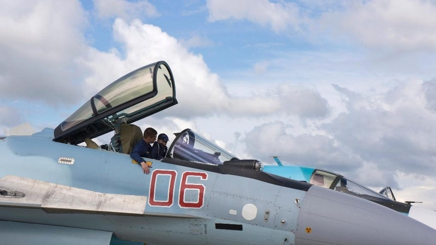A Russian air force officer sits with a boy in the cockpit of an Su-35 fighter jet after an air show at the Kubinka air base outside Moscow, Russia, Saturday, May 21, 2016. The Russian military's Strizhi, The Swifts, and Russkiye Vityazi, the Russian Knights, aerobatic teams marked their 25-year jubilee with an aerobatics performance that attracted enthusiastic crowds.  (AP Photo/Vladimir Isachenkov)