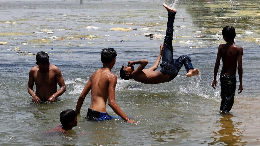 Indian children play in the Sabarmati river to beat the heat on a hot summer day in Ahmadabad, India, Friday, May 20, 2016. The prolonged heat wave this year has already killed hundreds and destroyed crops in more than 13 states, impacting hundreds of millions of Indians. (AP Photo/Ajit Solanki)