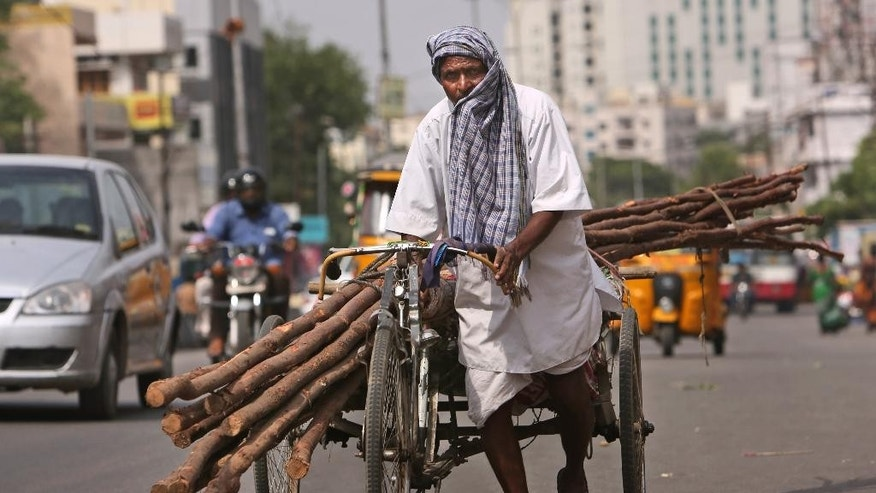 A laborer covers himself with a cloth to protect from the sun as he pulls a rickshaw carrying wooden logs on a hot summer afternoon in Hyderabad, India, Friday, May 20, 2016. The prolonged heat wave this year has already killed hundreds and destroyed crops in more than 13 states. The extreme heat has impacted hundreds of millions in western India  with record temperatures Friday reaching as high as a scorching 51 degrees Celsius (123.8 Fahrenheit). (AP Photo/Mahesh Kumar A.)