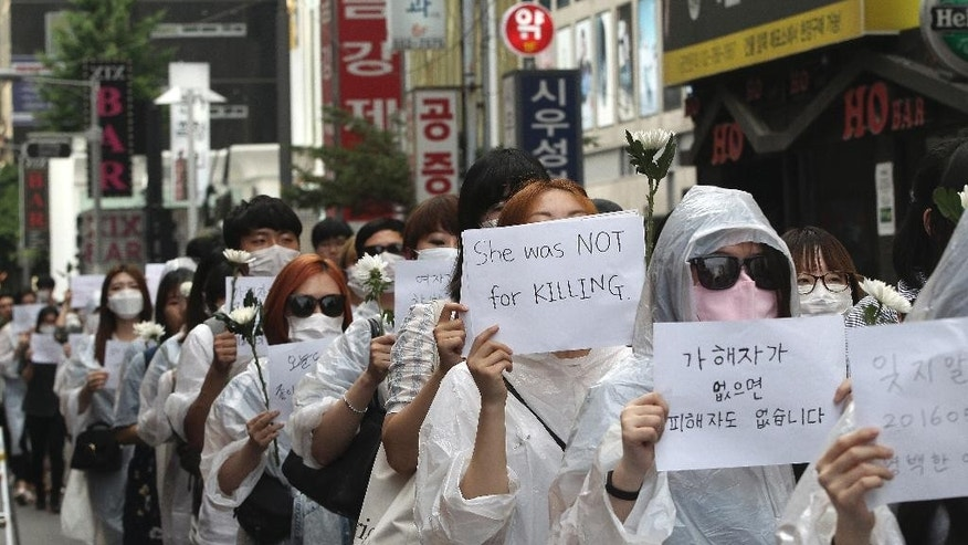 Mourners march during a rally to pay tribute to a South Korean woman who was stabbed to death near Gangham subway station in Seoul, South Korea, Saturday, May 21, 2016. Hundreds of South Koreans have marched in one of Seoul's busiest leisure districts to protest the stabbing death of a 23-year-old woman that struck a nerve in a country where many women live in fear of being attacked. (AP Photo/Ahn Young-joon)