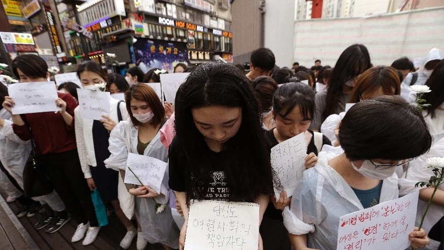 "Mourners pay a silent tribute to a South Korean woman who was stabbed to death during a rally near Gangham subway station in Seoul, South Korea, Saturday, May 21, 2016. Hundreds of South Koreans have marched in one of Seoul's busiest leisure districts to protest the stabbing death of a 23-year-old woman that struck a nerve in a country where many women live in fear of being attacked. The letters read ""Pray for the soul of the deceased.""(AP Photo/Ahn Young-joon)"