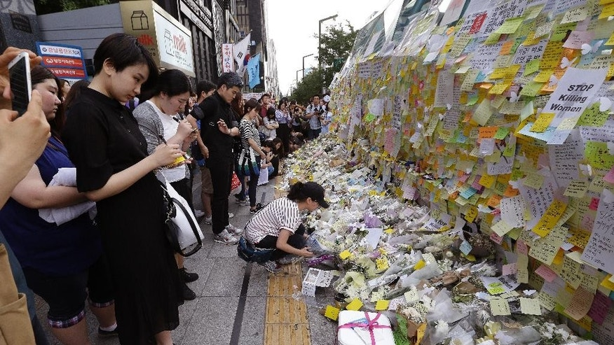 A woman places a flower for a South Korean woman who was stabbed to death at an exit of Gangham subway station in Seoul, South Korea, Saturday, May 21, 2016. Hundreds of South Koreans have marched in one of Seoul's busiest leisure districts to protest the stabbing death of a 23-year-old woman that struck a nerve in a country where many women live in fear of being attacked. (AP Photo/Ahn Young-joon)