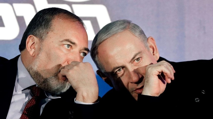 FILE - In this Wednesday, Jan. 16, 2013 file photo, Prime Minister Benjamin Netanyahu, right, and former Foreign Minister Avigdor Lieberman speak during a Likud-Yisrael Beitenu campaign rally in the port city of Ashdod.Israel's defense minister officially stepped down on Sunday, May 22, 2016 capping a tumultuous week of politics that is expected to result in the replacement of the former military chief with an inexperienced hard-liner in the sensitive post. Moshe Yaalon's departure cleared the way for Lieberman, one of Israel's most polarizing politicians, to take over as defense chief. (AP Photo/Tsafrir Abayov, File)