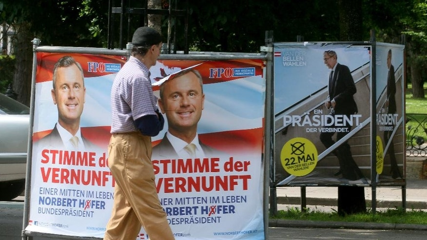 In this picture taken Thursday, May 19, 2016, a man walks past election posters of Alexander van der Bellen, candidate for the presidential elections and former head of the Austrian Greens, right, and Norbert Hofer, candidate for presidential elections of Austria's right-wing Freedom Party, FPOE, left, in Vienna, Austria, Thursday, May 19, 2016. Austrians will vote a new president on Sunday, May 22. (AP Photo/Ronald Zak)