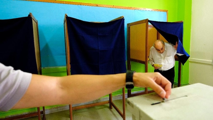 A voter exits a booth at a polling station during the parliamentary elections in the southern port city of Limassol in this mediterranean island of Cyprus, on Sunday, May 22, 2016. Cypriots elect a new parliament amid high voter disillusionment with what many see as the country's discredited political establishment. Some 543,000 voters are eligible to cast their ballots for 56 lawmakers. (AP Photo/Petros Karadjias)
