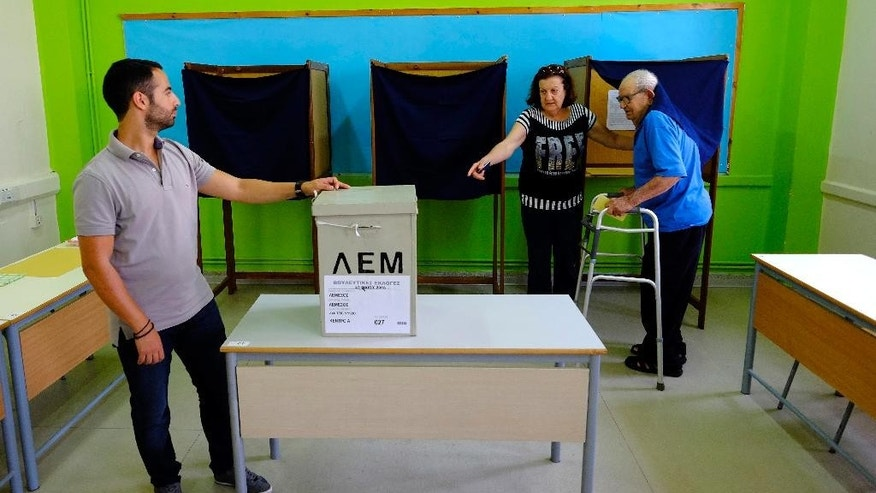 A man, helped by a woman, leaves the polling booth at a polling station during the parliamentary elections in southern port city of Limassol in this mediterranean island of Cyprus, on Sunday, May 22, 2016. Cypriots are voting for a new parliament amid public disillusionment with what many see as a discredited political establishment. Some 543,000 voters are eligible to cast their ballots for 56 lawmakers. (AP Photo/Petros Karadjias)