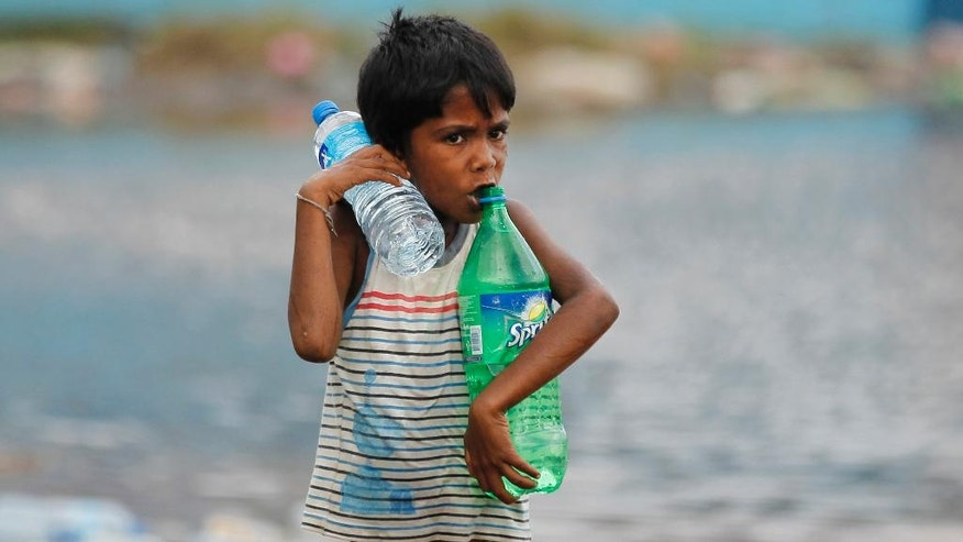 A Sri Lankan boy carries water bottles near a flood affected area near Colombo, Sri Lanka, Sunday, May 22, 2016. Sri Lanka's soldiers continued searching for scores of people missing since deadly landslides struck hill country several days ago leaving dozens dead. (AP Photo/Eranga Jayawardena)