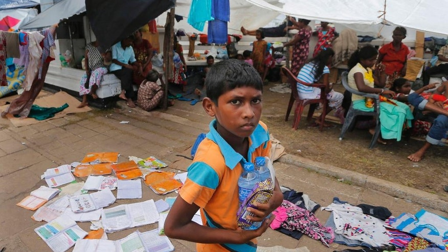 A Sri Lankan boy carries water bottles and a packet of food at a makeshift shelter for flood victims in Colombo, Sri Lanka, Sunday, May 22, 2016. Sri Lanka's soldiers continued searching for scores of people missing since deadly landslides struck hill country several days ago leaving dozens dead. (AP Photo/Eranga Jayawardena)