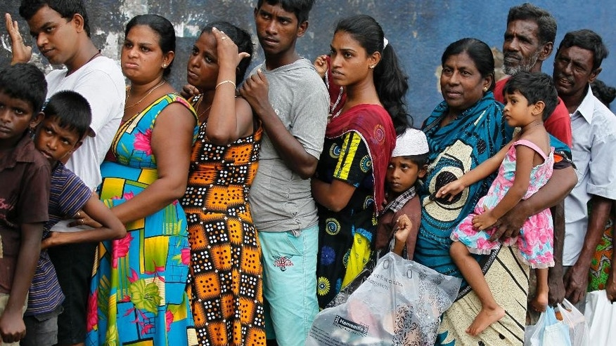 Sri Lankan flood victims line up to receive relief materials in a flood affected area near Colombo, Sri Lanka, Sunday, May 22, 2016. Sri Lanka's soldiers continued searching for scores of people missing since deadly landslides struck hill country several days ago leaving dozens dead. (AP Photo/Eranga Jayawardena)