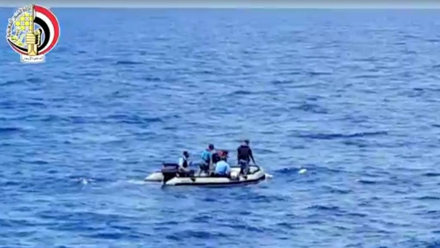 This still image taken from video posted Saturday, May 21, 2016, on the official Facebook page of the Egyptian Armed Forces spokesman shows an Egyptian dinghy collecting wreckage of EgyptAir flight 804. Smoke was detected in multiple places on EgyptAir flight 804 moments before it plummeted into the Mediterranean, but the cause of the crash that killed all 66 on board remains unclear, the French air accident investigation agency said on Saturday.  (Egyptian Armed Forces via AP)
