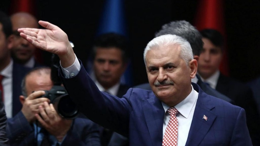 Binali Yildirim, Turkey's current Transportation Minister and founding member of the AKP, Turkey's governing party, salutes during a meeting in Ankara, Turkey, Thursday, May 19, 2016.  Yildirim is expected to stand unopposed for the party leadership and automatically become Prime Minister at an extraordinary meeting to be held Sunday in Ankara. The shake up comes after Prime Minister Ahmet Davutoglu stepped down on May 4. (AP Photo)