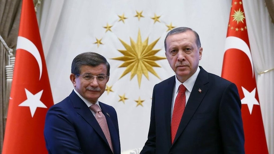 Turkish President Recep Tayyip Erdogan, right, and Prime Minister Ahmet Davutoglu shake hands as they pose for a photograph during a final farewell in Ankara, Turkey, Thursday, May 19, 2016. Davutoglu stepped down on May 4 over differences with Erdogan who is pushing for a constitutional overhaul that would concentrate greater powers in his hands.(Kayhan Ozer/Pool Photo via AP)