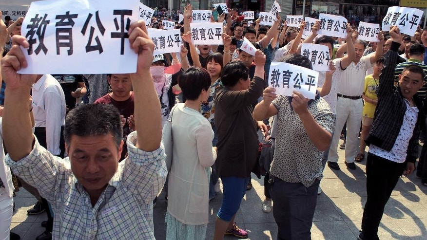 "People hold signs reading ""fair education"" as they hold a protest in Erqi Square in Zhengzhou, central China's Henan province, Sunday, May 22, 2016. Around 500 people protested what they say is a lack of university student placements in their central China province during the latest protest over education reform. (Chinatopix via AP) CHINA OUT"