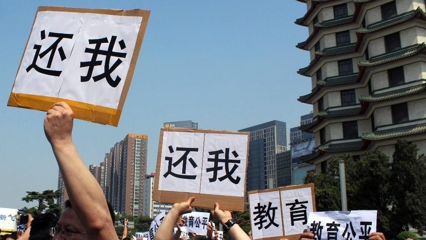 "People hold signs reading ""return me"" and ""fair education"" as they protest in Erqi Square in Zhengzhou, central China's Henan province, Sunday, May 22, 2016. Around 500 people have protested what they say is a lack of university student placements in their central China province in the latest protest over education reform. (Chinatopix via AP) CHINA OUT"