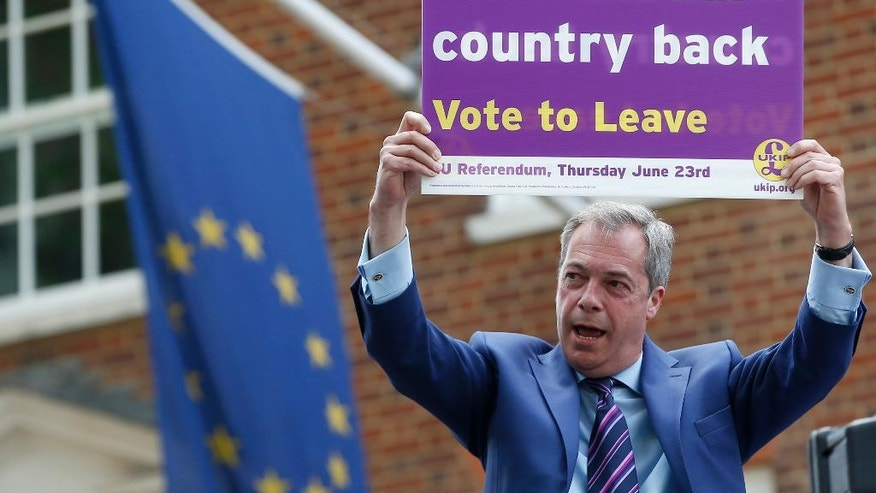 British politician and leader of the UKIP party Nigel Farage holds up a placard as he launches his party's campaign for Britain to leave the EU, outside the EU representative office in London, Friday, May, 20, 2016. Britain will vote on wether to remain or leave the EU on June 23. (AP Photo/Alastair Grant )