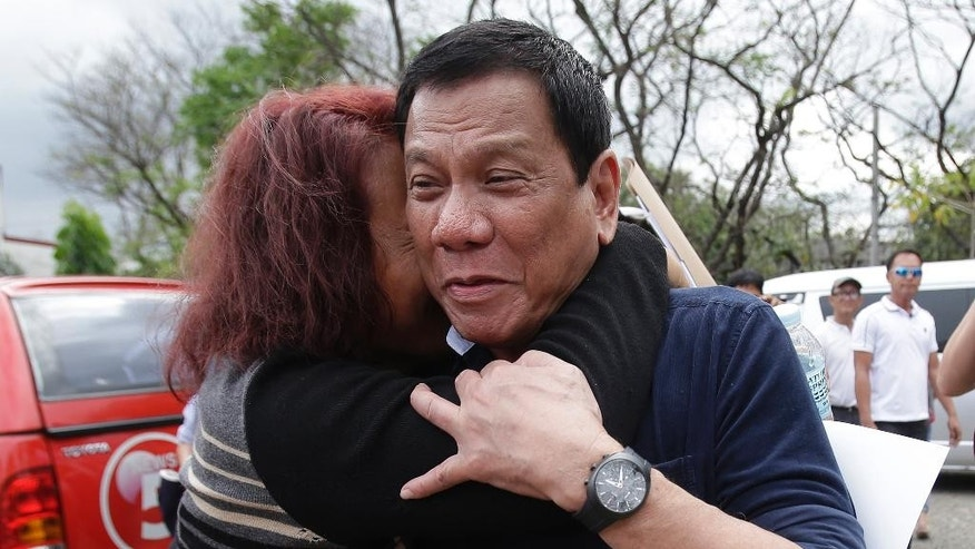 "FILE - In this Feb. 18, 2016 file photo, Philippine presidential candidate Rodrigo Duterte, right, is hugged by a supporter before attending a forum at the University of the Philippines in suburban Quezon city, north of Manila, Philippines. Duterte kept Filipinos guessing for months last year whether he would run for president. He repeatedly declared that he wouldn't, then cited different reasons when he finally did. On the campaign trail, he flipped and flopped on a number of key pronouncements. That has made it difficult to discern when the brash Duterte, who spikes his speeches with sarcasm and hyperbole for added punch, is serious or, in his own words, is ""just taking you for a ride."" (AP Photo/Aaron Favila, File)"