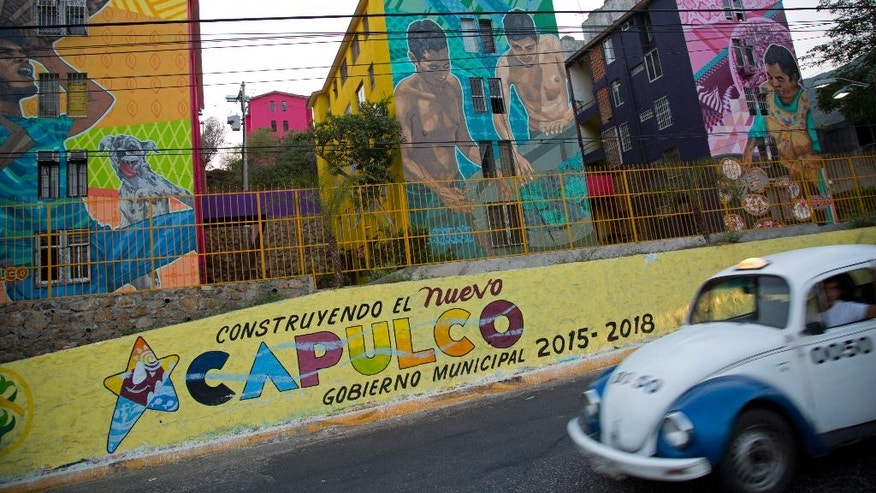 "In this May 11, 2016 photo, a taxi drives past the Cuauhtemoc Housing Unit and a municipal sign with a message that reads in Spanish; ""Building the new Acapulco"" in Acapulco, Mexico. The city's latest wave of killings began April 24, when bursts of gunfire broke out along the coastal boulevard. The murder rate in this city of 800,000 hit 146 per 100,000 inhabitants in 2012. It has since fallen to about 112 per 100,000, but that remains far higher than nationwide levels. (AP Photo/Enric Marti)"