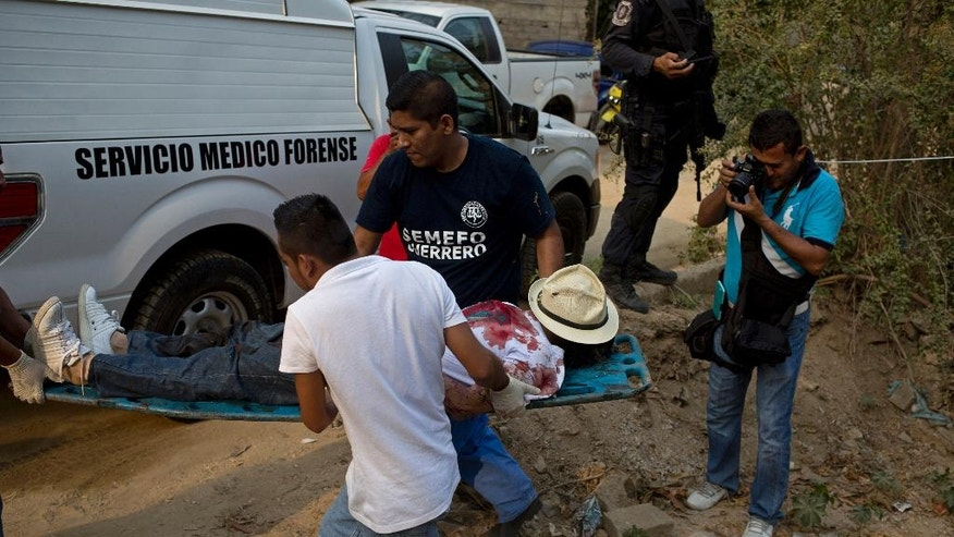 In this May 9, 2016 photo, forensic workers remove the body of a man shot four times in an empty lot between residences in the Leyes de Reforma neighborhood of Acapulco, Mexico.  Joaquin Badillo, who runs Acapulcoís leading private security firm, estimated that 95 percent of the killings in the city are linked directly or indirectly to criminal gangs. ìSomebody didnít live up to a deal, somebody didnít pay, somebody didnít deliver, somebody was given (drugs) to sell and didnít, somebody else went to work for the competition,î Badillo said. ìNone of these people are doing Acapulco any good.î (AP Photo/Enric Marti)