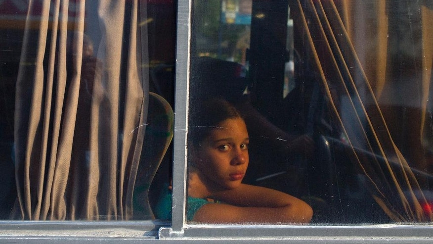"In this May 10, 2016 photo, a girl stares out a bus window during a routine police checkpoint on the ""costera,"" the seaside boulevard that runs through the hotel zone in Acapulco, Mexico. Today it's almost easier to find a truck full of soldiers, a federal policeman or a gaggle of local tourist cops than it is to find a taxi along the seaside boulevard. (AP Photo/Enric Marti)"