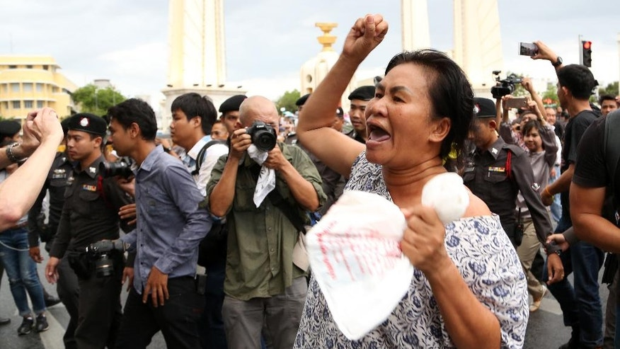A pro-coup demonstrator chants as she is led away from anti-coup protesters at Democracy Monument during a ceremony to mark the second anniversary of the military take over of government in Bangkok, Thailand, Sunday, May 22, 2016. Thailand's military seized power from an elected government on May 22, 2014, with the justification that it wanted to end chaotic and violent political confrontations that had wracked the country for years. (AP Photo/Mark Baker)