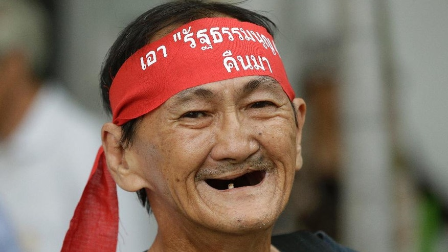 "Wearing a headband that reads: ""bring back the constitution,"" a demonstrator smiles during a protest to mark the second anniversary of the military take over of government in Bangkok, Thailand, Sunday, May 22, 2016. Thailand's military seized power from an elected government on May 22, 2014, with the justification that it wanted to end chaotic and violent political confrontations that had wracked the country for years. (AP Photo/Mark Baker)"