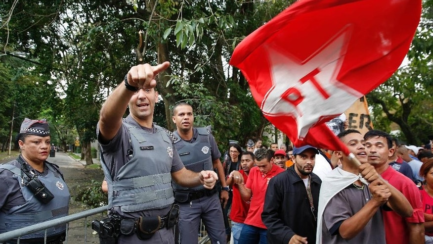 Stopped by a police barricade, demonstrators shout slogans as one of them waves a Workers Party flag, during a protest against Brazil's acting President Michel Temer and in support of Brazil's suspended President Dilma Rousseff, close to Temer's residence in Sao Paulo, Brazil, Sunday, May 22, 2016. Temer took office after Rousseff was suspended for up to 180 days while the Senate holds an impeachment trial. (AP Photo/Andre Penner)