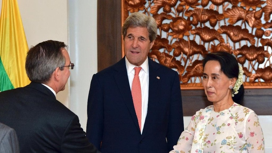 U.S. Secretary of State John Kerry, center, watches Myanmar's Foreign Minister and de facto leader Aung San Suu Kyi, right, and U.S. Ambassador to Myanmar Scot Marciel shake hands during a meeting in Naypyitaw, Myanmar, Sunday, May 22, 2016. Kerry on Sunday urged Myanmar's new civilian-led government to complete the Southeast Asian nation's transition to democracy by implementing further reforms to enshrine free markets, development and human rights. (AP Photo/Aung Shine Oo, Pool)