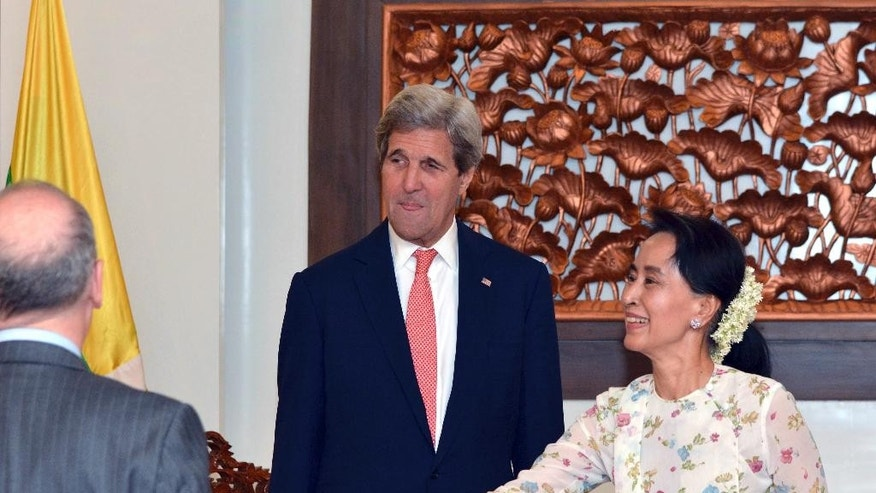 U.S. Secretary of State John Kerry, center, watches Myanmar's Foreign Minister and de facto leader Aung San Suu Kyi, right, reach to shake hands with a member of  U.S. delegation during a meeting in Naypyitaw, Myanmar, Sunday, May 22, 2016. Kerry on Sunday urged Myanmar's new civilian-led government to complete the Southeast Asian nation's transition to democracy by implementing further reforms to enshrine free markets, development and human rights. (AP Photo/Aung Shine Oo, Pool)